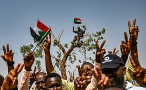 Sudanese protesters chant slogans and flash victory signs as another waves a national flag from a tree