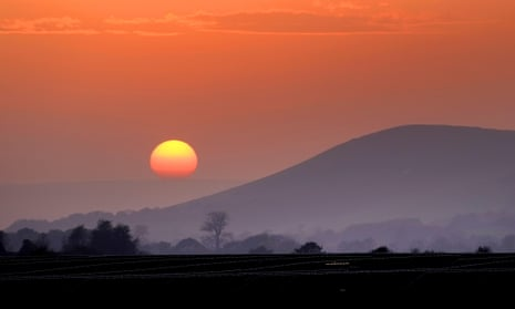 The sun setting behind Mount Caburn, near Lewes, in the South Downs.