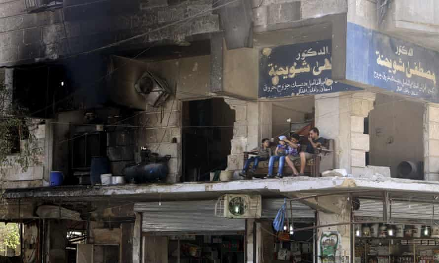 Residents sit on a sofa on a balcony of a damaged building in Aleppo's al-Shaar neighbourhood in Syria.