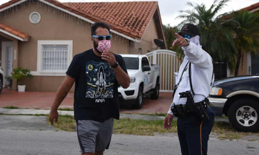 A policeman directs a citizen where to pick up an unemployment form in Miami, Florida, earlier this month.