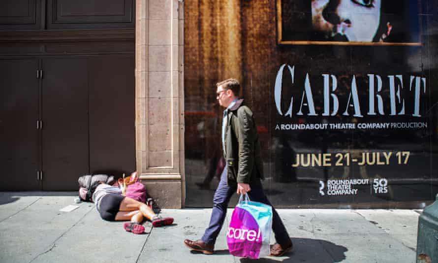 A man walks by a homeless woman sleeping on the sidewalk San Francisco's Tenderloin district.