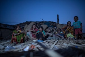 Families rest among the rubble in the village of  Bhaluhi.