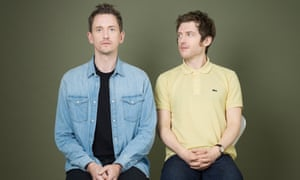John Robins, wearing a blue denim shirt and Elis James, in a yellow polo shirt, sitting side by side