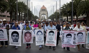 The relatives of 43 missing college students carry photographs of their missing loved ones in Mexico City, six months after they disappeared. Behind them stands the Monument to the Revolution.