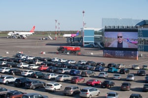 The audience waits in their cars on the apron area of Vilnius international airport in Lithuania