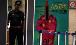 A security guard at the entrance to a cinema in Mumbai next to a poster for Lipstick Under My Burkha