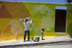 German Crew artist collective member Carlos Duarte paints a section of a gigantic mural