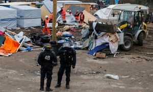 Riot police secure the area as workers tear down shelters at the refugee camp in Calais.