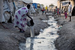 A woman empties dishwater into a trench of dirty water at Malakal camp
