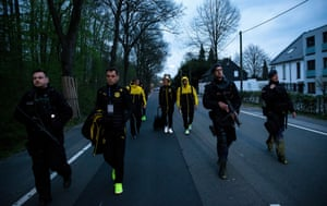 Sven Bender, Marcel Schmelzer and Nuri Sahin of Borussia Dortmund are escorted by police after the team bus was damaged by an explosion.