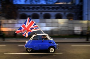 London, UK: a man waves union flags as he drives past Brexit supporters gathering in Parliament Square