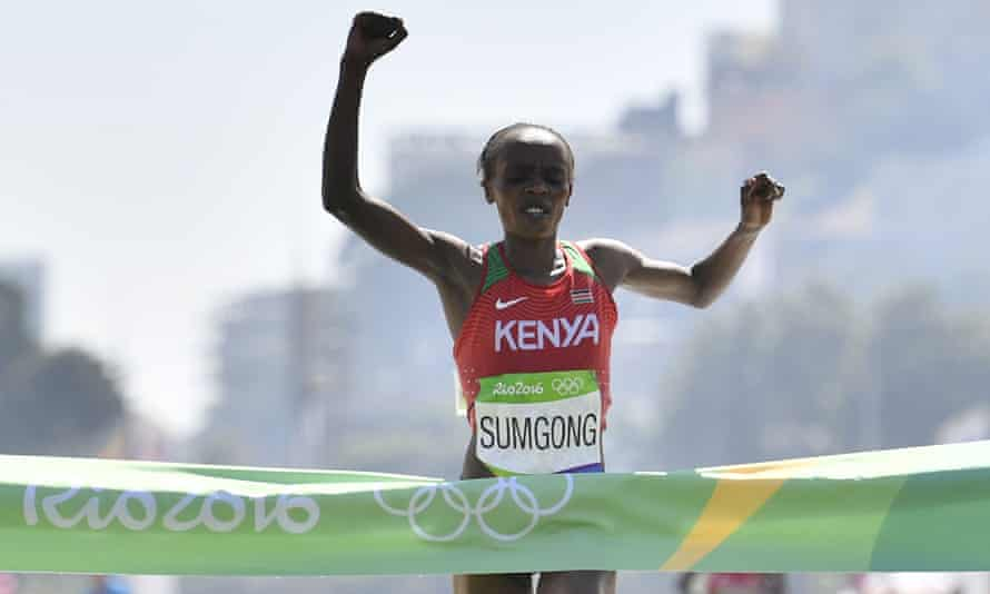 Kenya's Jemima Sumgong raises her arms in victory as she crosses the finish line of the Women's Marathon at Rio 2016.