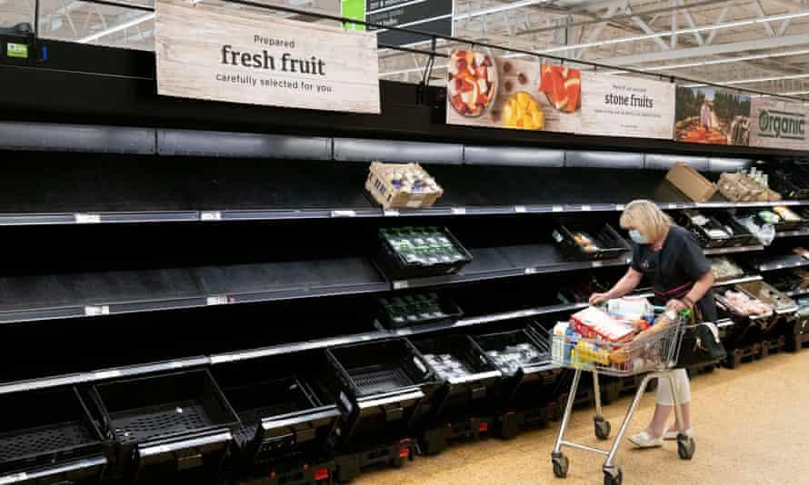 A woman wearing a face mask near empty fruit and veg shelves in an ASDA store.