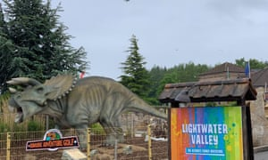 A dinosaur statue near a ride at the Lightwater Valley theme park