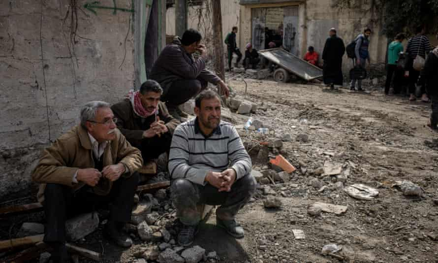 Men in the street as excavators dig through the rubble.