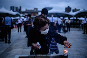 A visitor burns incense to pay tribute to the atomic bomb victims at the Hiroshima Peace Memorial Park