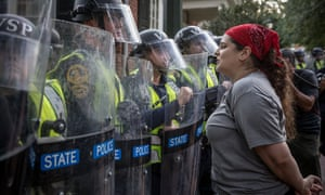 A demonstrator at UVA asks riot police to leave on the University of Virginia campus during protests in Charlottesville, Virginia, on Saturday.
