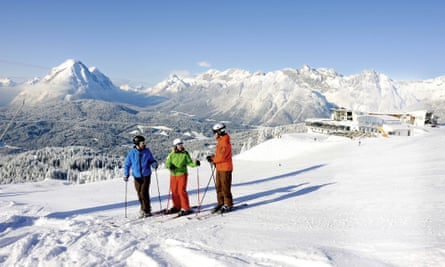 Three skiers about to set off in deep snow, mountains behind