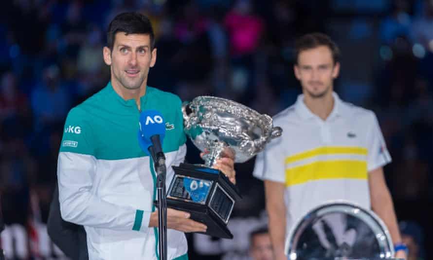Novak Djokovic poses with the Australian Open trophy as beaten finalist Daniil Medvedev watches on.
