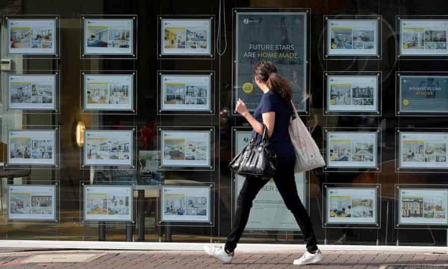 a woman passes an estate agents