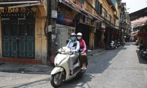 People pass closed bars on a scooter in Hanoi, Vietnam on Thursday. An outbreak in the city of Da Nang has grown to over 40 cases in six cities and authorities are beginning to reimpose broader restrictions.