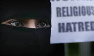 A Muslim woman wearing a niqab veil protests outside Bangor Street Community centre against comments Jack Straw made about the veil.