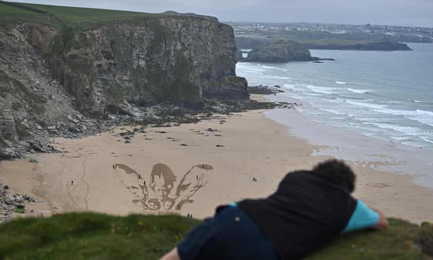 A sand drawing calls on world leaders to 'share the vaccine and waive the patent' at Watergate Bay near Newquay, Cornwall.