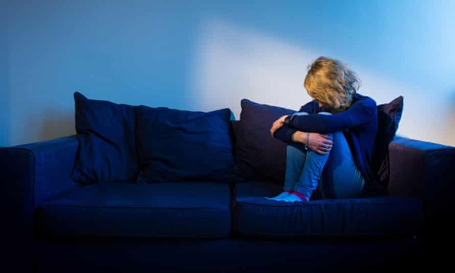 A young woman showing signs of depression sits alone on a sofa