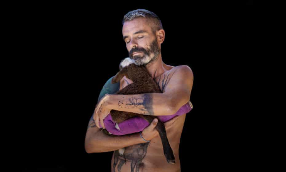 Armoni the lamb being held in the arms of Gaia animal sanctuary founder Coque Fernandez Abella, in Spain