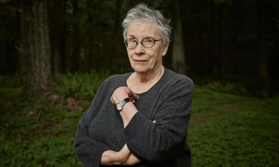 Annie Proulx in a jumper, with short hair and wearing glasses, arms crossed and with a quizzical expression