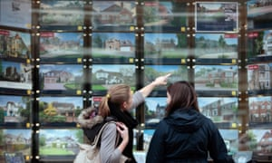 Pedestrians browse residential properties in the window of an estate agent.