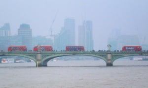 Anne Ross: Buses queuing on a bridge over the Thames in London on a foggy autumn day.