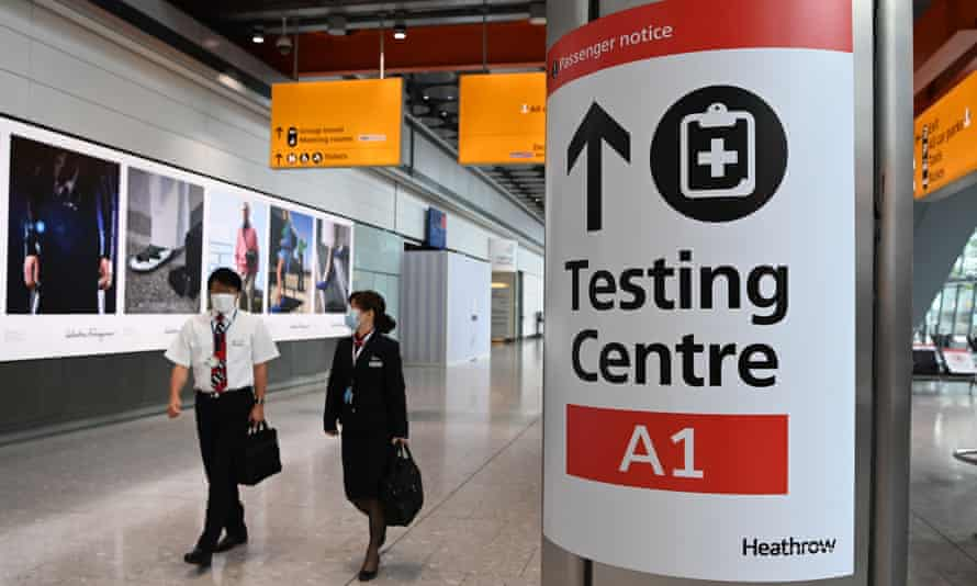 cabin crew pass a covid test centre sign at heathrow