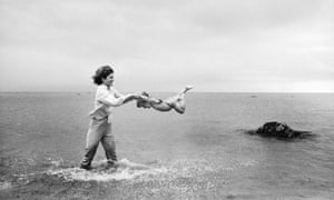 Jackie Kennedy swings her daughter Caroline in the shallows at Hyannis Port in 1959.