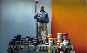 In his St Ives studio, Trevor Bell, paintpots and brushes at the ready, demonstrates the scale of his work, including in the background two of his 'quiet five' paintings.