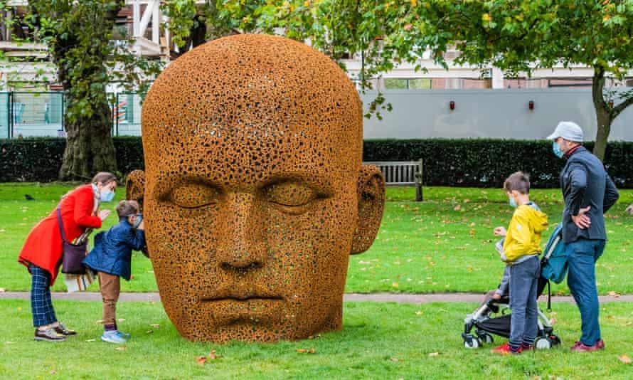 A family look at a massive head sculpture