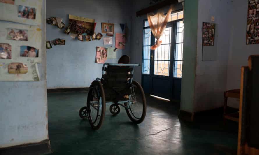 A child waits alone at an orphanage in Kampala.