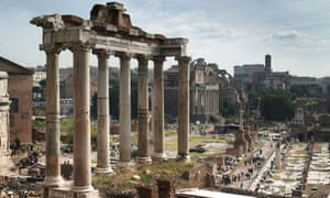 The Temple of Saturn with the Colosseum in the far distance. The Forum, Rome, Italy.