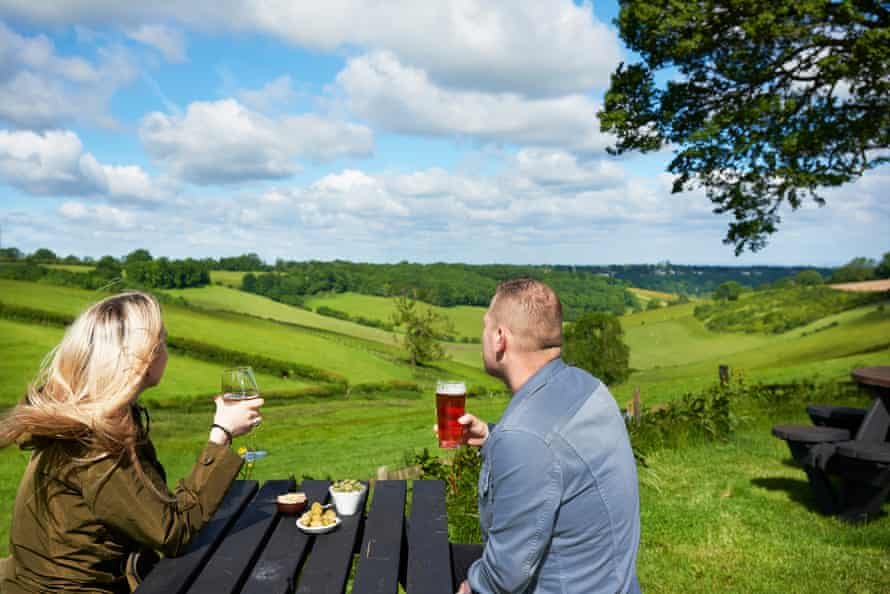 A couple at a table with drinks and food looking at view from Botley Hill Farmhouse, Surrey.