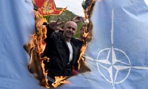 Demonstrators burn a Nato flag
