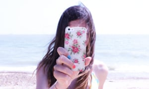 Girl taking photo with her mobile phone, face hidden behind the screen, with the ocean as a backdrop