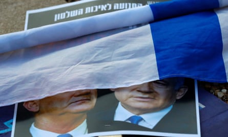 A rolled Israeli flag lies upon a placard left on the street with a picture of Prime Minister Benjamin Netanyahu and his rival-turned-partner Benny Gantz
