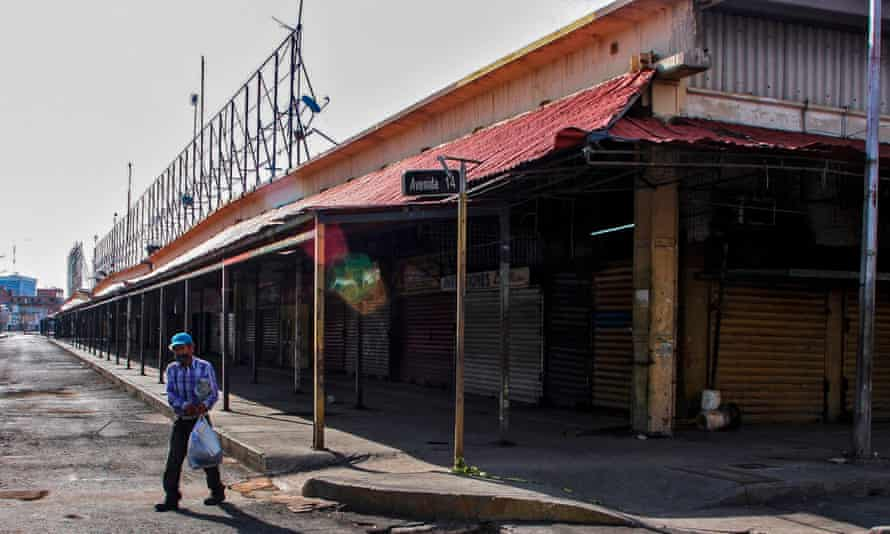 A man walks outside the empty flea market in Maracaibo on 2 July.