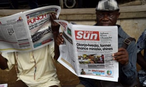 A man reads a newspaper with a front-page story about the appointment of Ngozi Okonjo-Iweala as WTO president