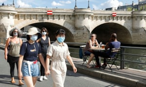 Pedestrians wearing protective face masks walk along the Seine river banks in Paris, as France reinforces mask-wearing as part of efforts to curb a resurgence of coronavirus.