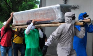 Relatives of a person who died from the new coronavirus carry the wrapped coffin inside a cemetery in the north of Guayaquil.