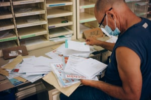 Cyril's father, Yoland, helps to sort mail in the Salazie postal centre.