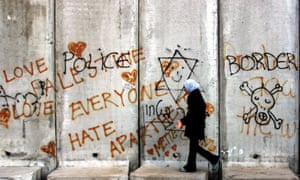 A Palestinian woman walks along a section of Israel's controversial barrier by the West Bank town of Abu Dis, on the edge of Jerusalem, in 2005.