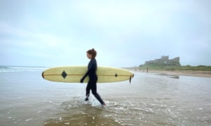 Young woman in wetsuit with board, BAMBurgh castle in background.