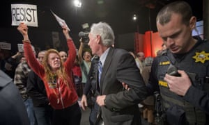 Police escort Republican congressman Tom McClintock through an audience in the Tower Theatre in Roseville, California.